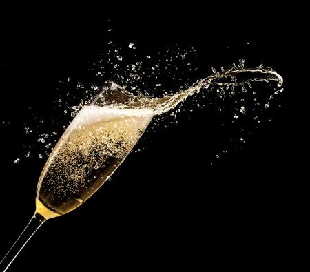 Glas champagne met splash, geïsoleerd op zwarte achtergrond