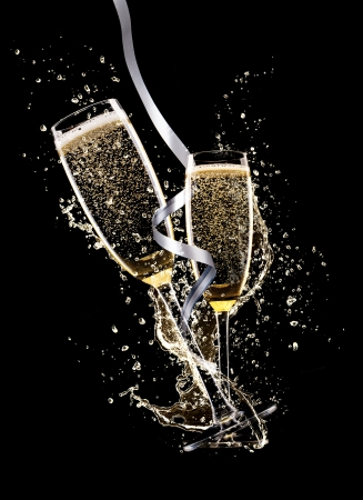 champagne glass: Glasses of champagne with splash, isolated on black background