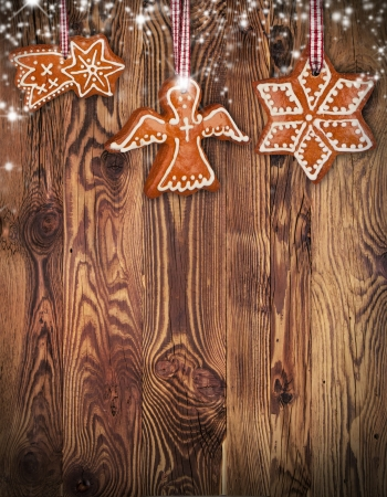 Traditional gingerbread hanging on wooden background photo