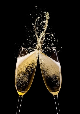 Glasses of champagne with splash, isolated on black background
