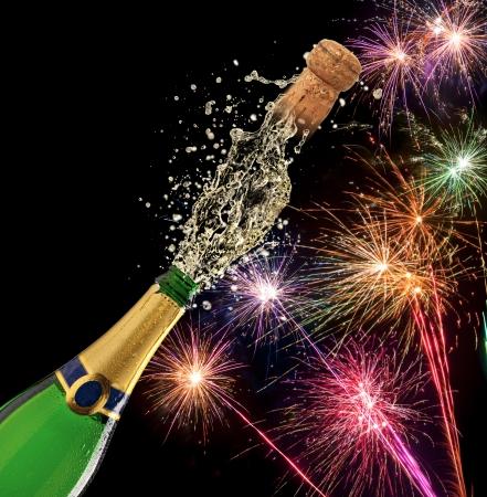 Flasche Champagner mit Spritzer und Feuerwerk auf schwarzem Hintergrund
