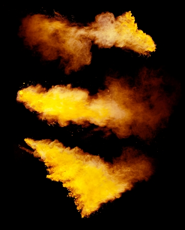 Freeze motion of yellow dust explosion isolated on black background photo
