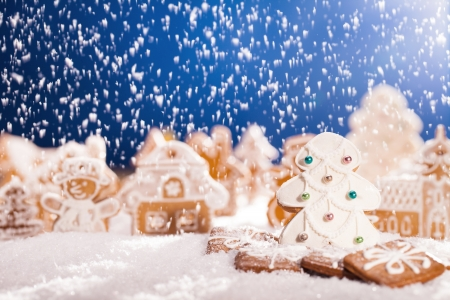Macro photo of gingerbread village with falling snow photo