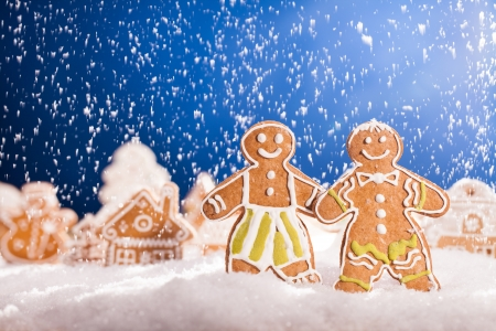 Macro photo of gingerbread village with falling snow Stock Photo