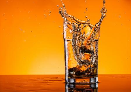 Glass of whiskey splashing out photo