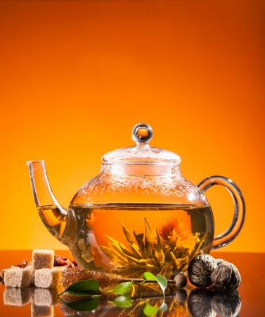 Teapot with blooming tea on glass photo