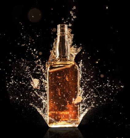 botella de whisky: Aislado disparo de whisky con salpicaduras en negro