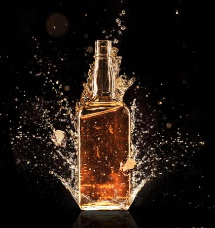 Isolated shot of whiskey with splash on black photo