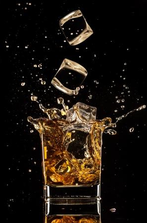 cubetti di ghiaccio: Isolato colpo di whisky con spruzzata su nero