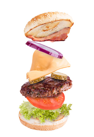 high calorie: Flying ingredients in hamburger, isolated on white background