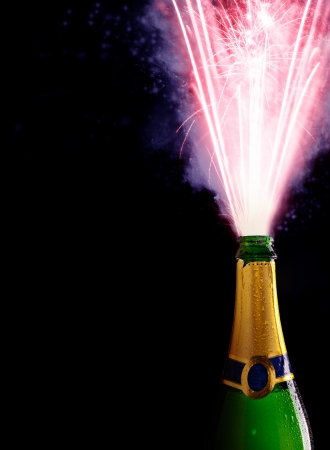 Champagne bottle with blasting fire, isolated on black background photo