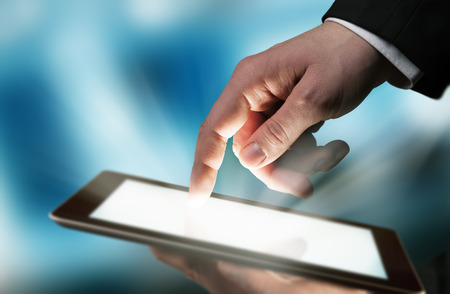 Business concept with man hand touching tablet computer photo