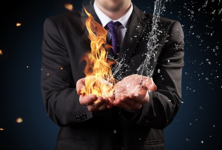 Businessman with fire and water in hands  Concept of threats and solutions as so as manager responsibility and power