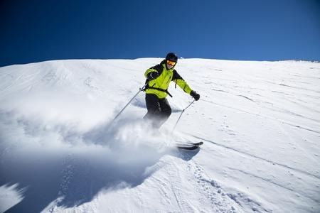 downhill skiing: Alpine skier skiing downhill, blue sky on background Stock Photo
