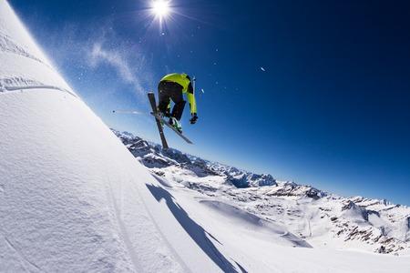 powder snow: Alpine skier in high jump, blue sky on background