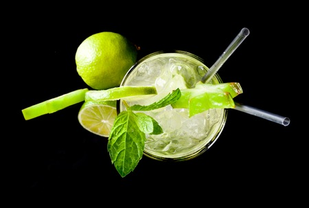Studio shot of fresh mojito drink with slime slices, isolated on black background