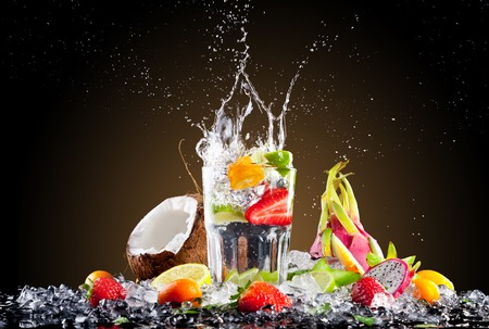 Studio shot of tropical cocktail with ice cubes and splash  photo