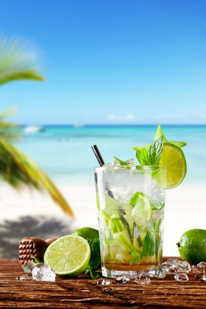 Mojito drink on wood with blur beach background Фото со стока
