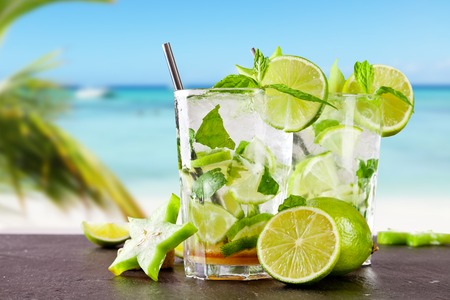 Mojito drink on wood with blur beach background Imagens