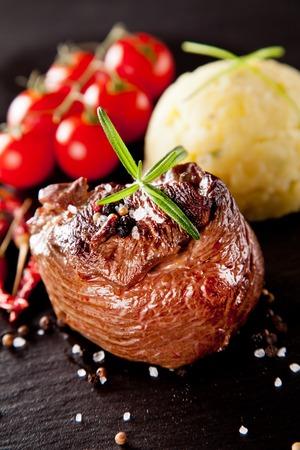carne roja: Pedazo de la carne roja con el romero servido en superficie de piedra negro Foto de archivo