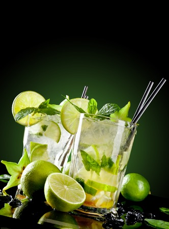 Studio shot of fresh mojito drinks with slime slices, isolated on black background