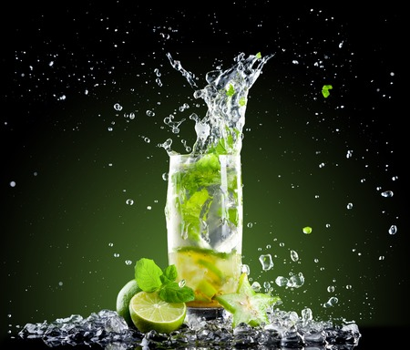 Studio shot of fresh mojito drink with ice cubes and splash on black background Imagens