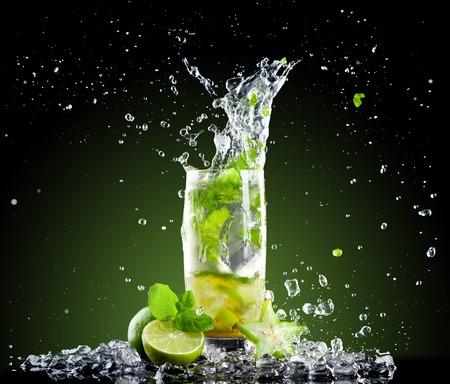 Studio shot van verse mojito drinken met ijsblokjes en splash op zwarte achtergrond Stockfoto