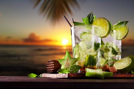 Mojito drankjes op hout met avond onscherpte oceaan wal achtergrond