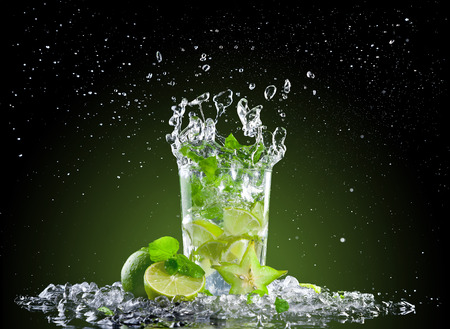 Studio shot of fresh mojito drink with ice cubes and splash on black background photo