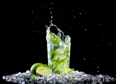Studio shot of fresh mojito drink with ice cubes and splash on black background Фото со стока