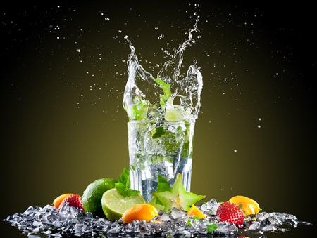 Studio shot of fresh mojito drink with ice cubes and splash on black background photo