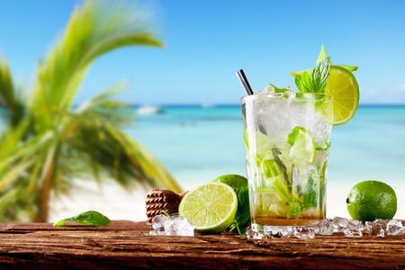 Mojito drink on wood with blur beach background 스톡 콘텐츠
