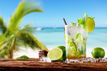 cocktail fruit: Bebida Mojito sobre madera con fondo de playa desenfoque