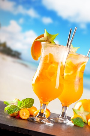 Fresh summer orange drinks, blur beach on background photo