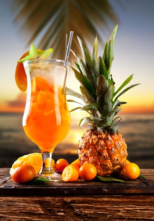 Fresh summer orange drink, blur beach on background photo