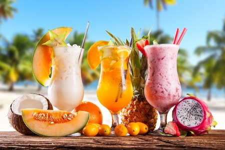 Exotic summer drinks served on wood  Blur sandy beach as background photo