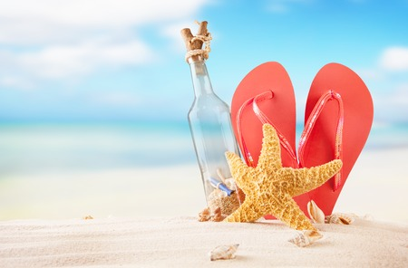 Summer concept with sandy beach, glass bottle, shells and starfish  photo