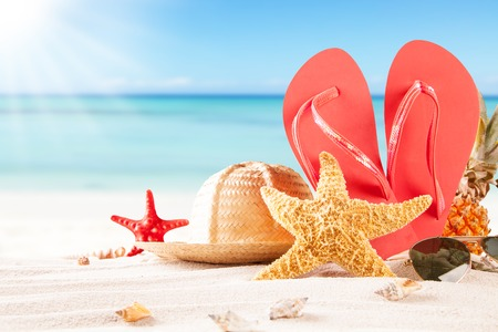 Summer concept of sandy beach, straw hat, shells and starfish