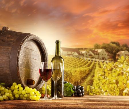krajina: Starý dřevěný soudek s lahví a sklenicí červeného, bílého vína venkova, vinici na pozadí