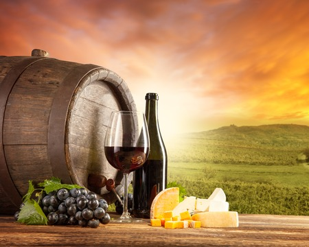 Old wooden keg with bottle and glass of red wine  Rural vineyard on background