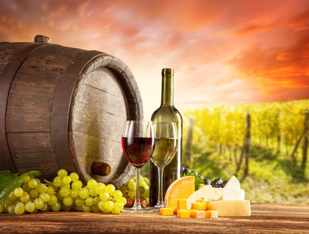 wine country: Old wooden keg with bottle and glass of red, white wine  Rural vineyard on background