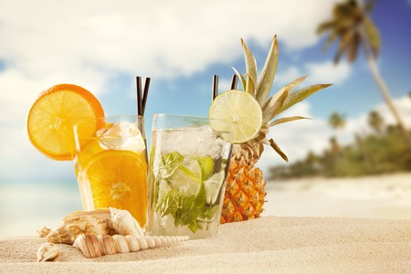 Exotic summer drinks with sea shells and stars, blur sandy beach