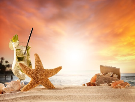 Summer concept with sandy beach, shells and mojito drink photo