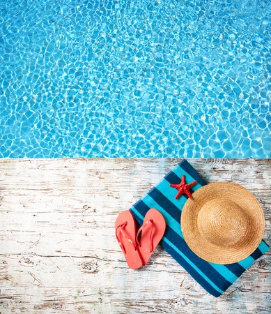 red straw: Concept of summer accessories on wood with blue water as background Stock Photo