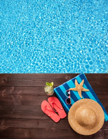 straw: Concept of summer accessories on wood with blue water as background Stock Photo