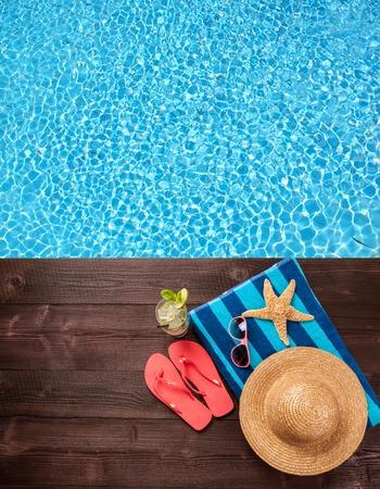 Concepto de accesorios de verano en la madera con el agua azul como fondo