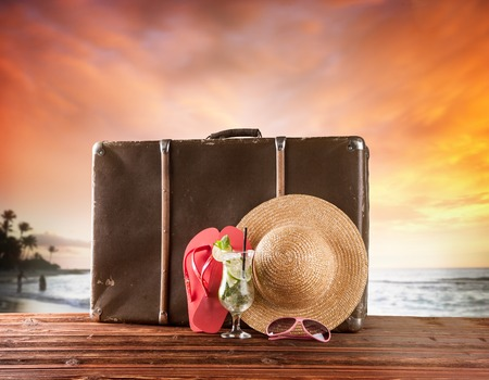 Concept of summer travelling with old suitcase and accessories  Blur beach on background Stock Photo