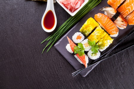 black dish: Various kinds of sushi food served on black stone