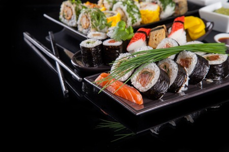 Various kind of sushi food served on black background photo
