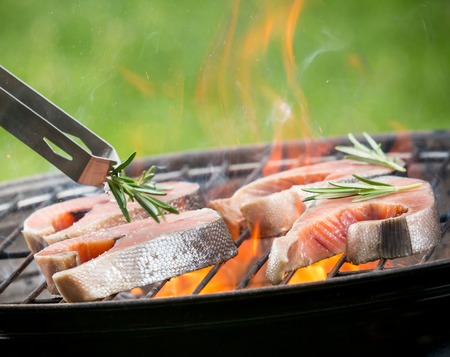 fish fire: Delicious grilled salmon steaks on fire Stock Photo